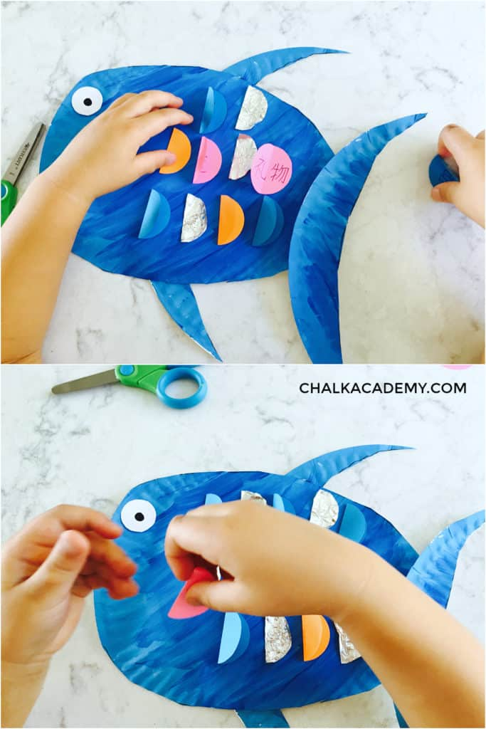 Putting fins on paper plate rainbow fish craft