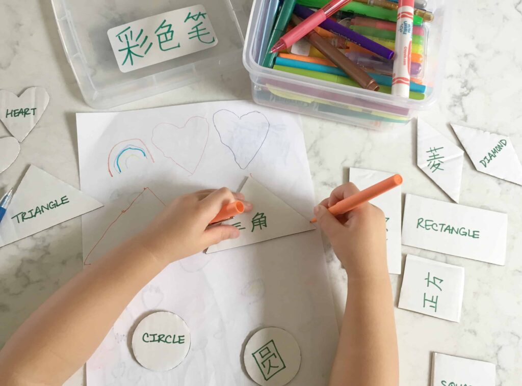 Child using bilingual cardboard triangle shape template