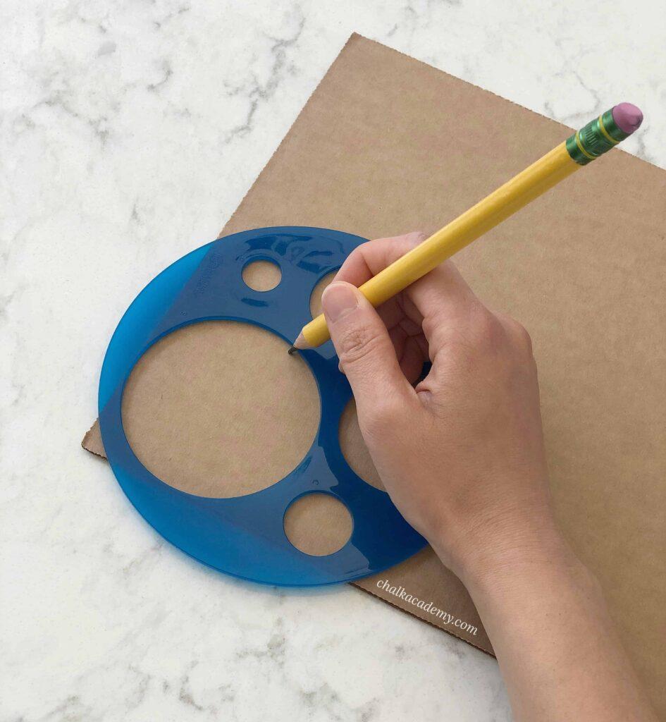 Tracing circle shape template onto cardboard