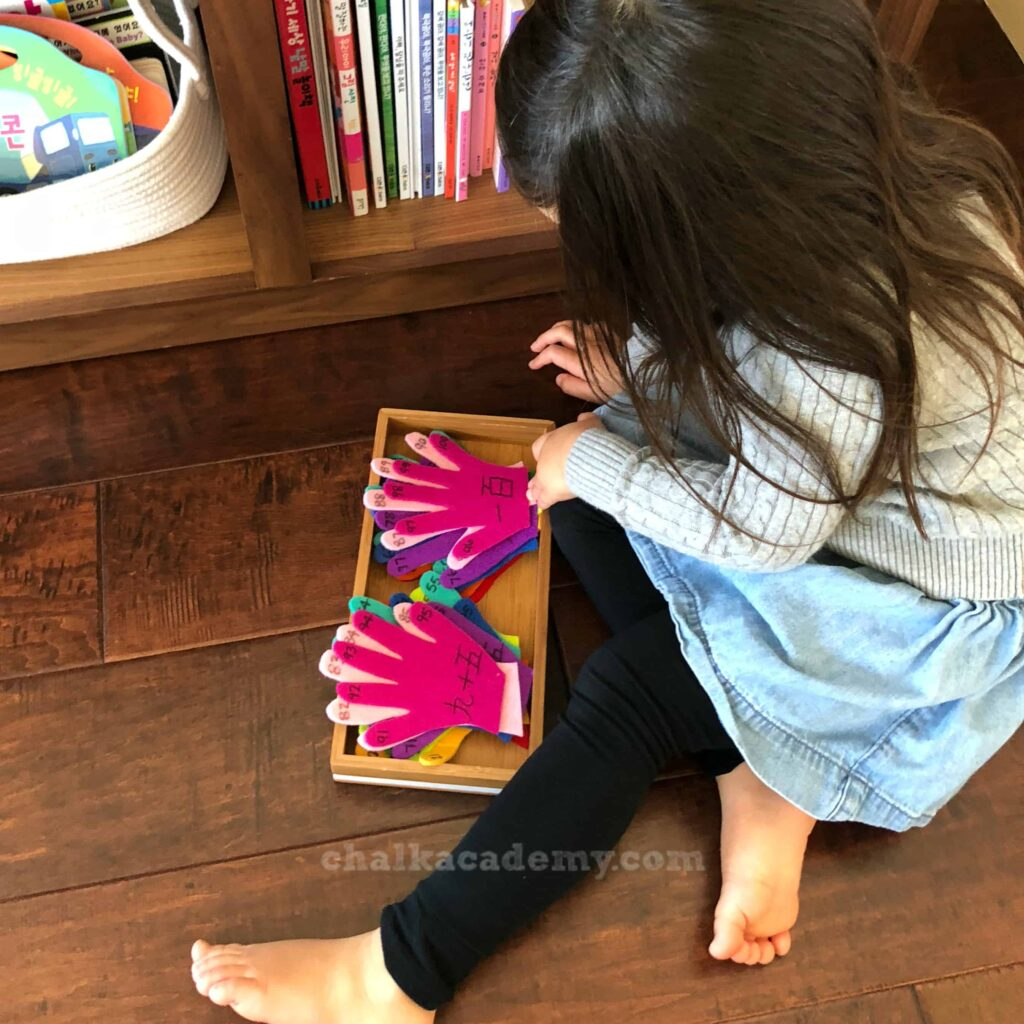 Felt hands organized neatly in Montessori-inspired tray
