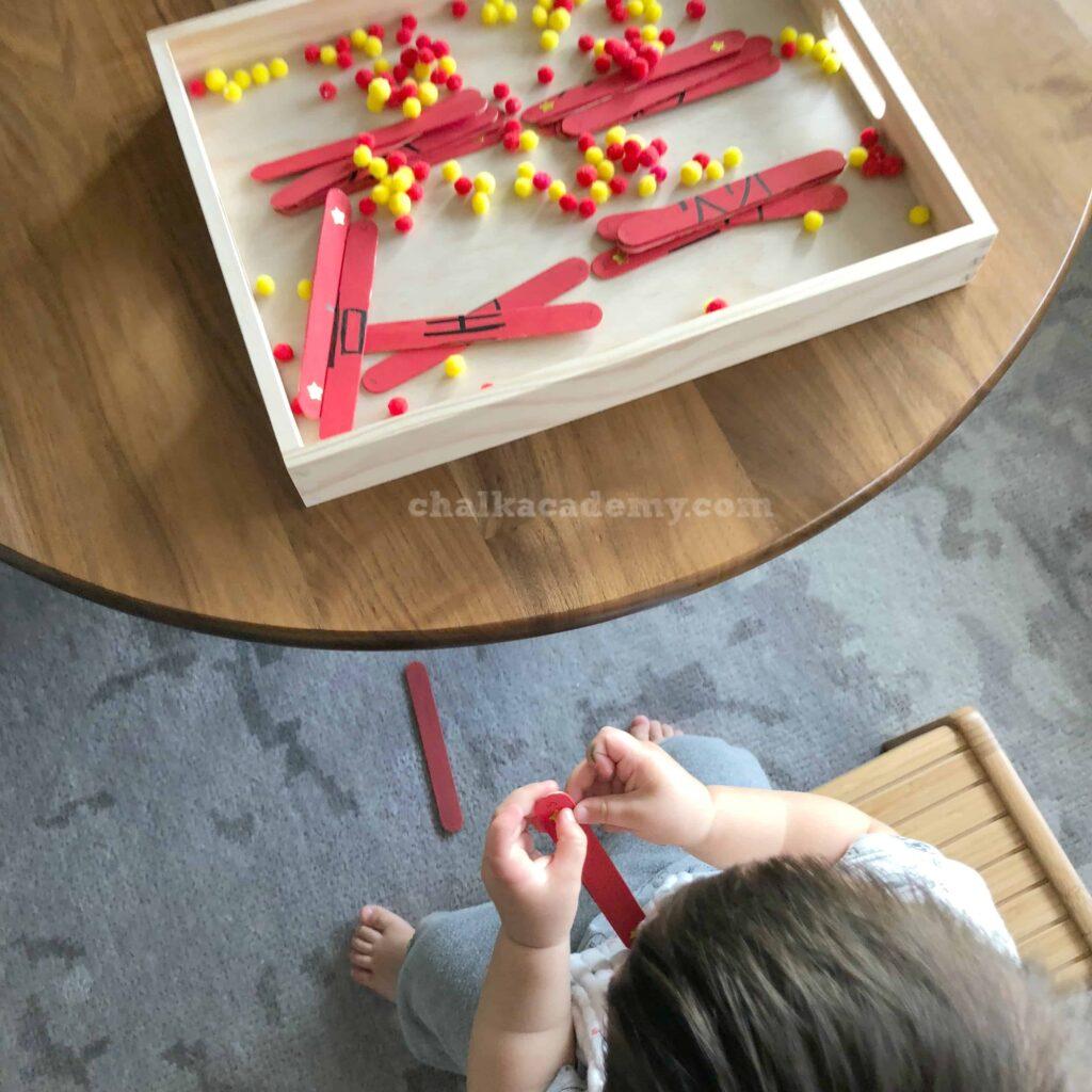 Toddler playing with craft sticks