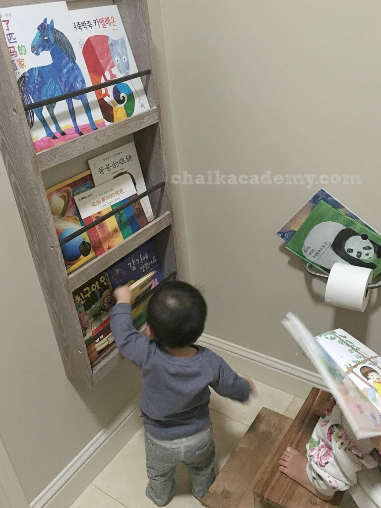 Front-facing bookcase in bathroom - motivate child to read by rotating books