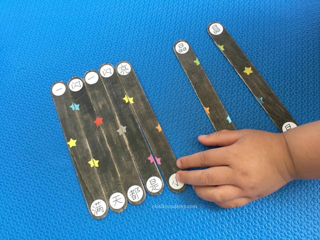 My young child completing the craft stick puzzle with Chinese lyrics