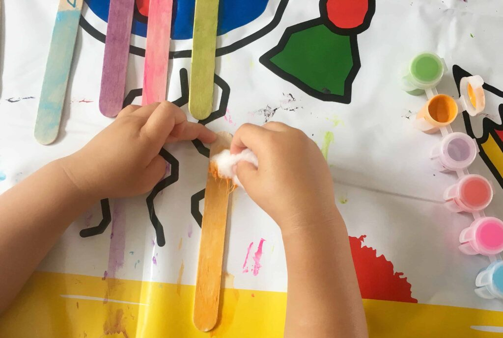 Painting popsicle sticks with cotton balls