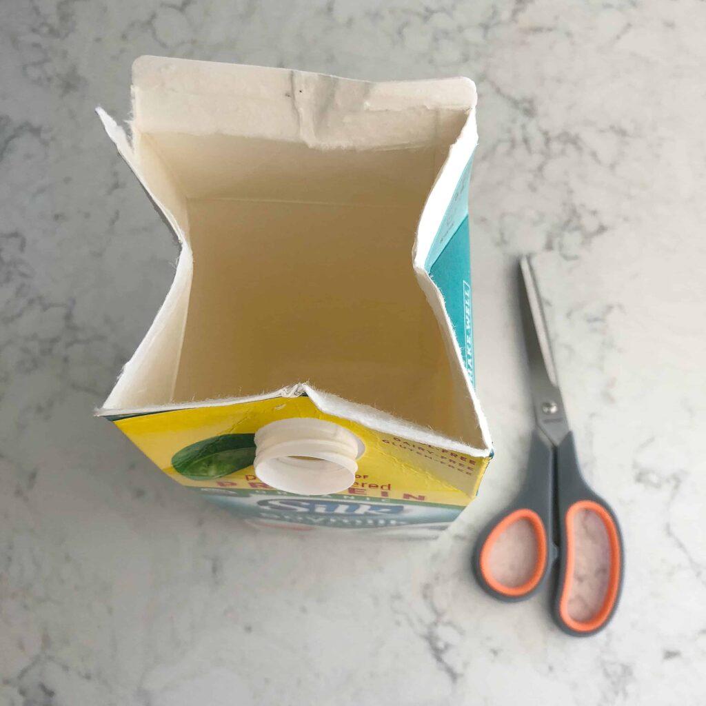 Open top of milk carton to make it easier to cut bottle caps