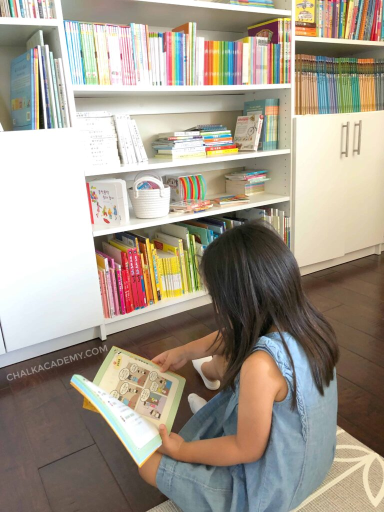 Girl reading comic book in library - motivate child to read by offering a variety of books that they love