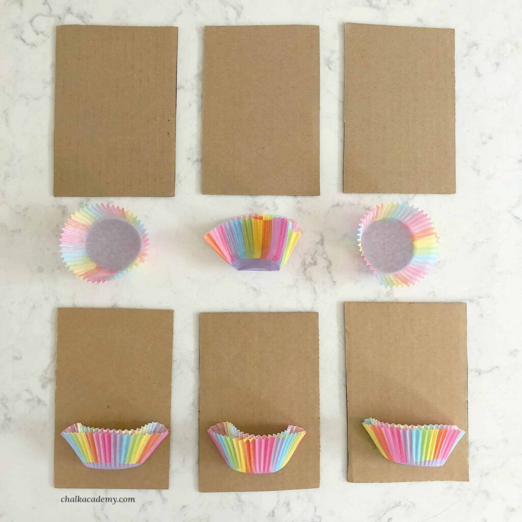 6 pieces of rectangular cardboard and 6 rainbow cupcake liners