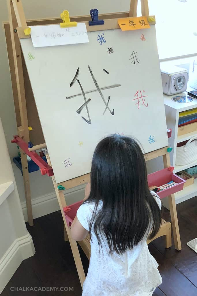 Writing 我  (Wǒ / Me) on the easel