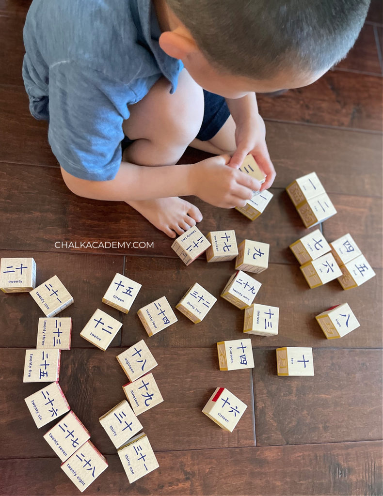 Child playing and learning with Uncle Goose Chinese character wood blocks