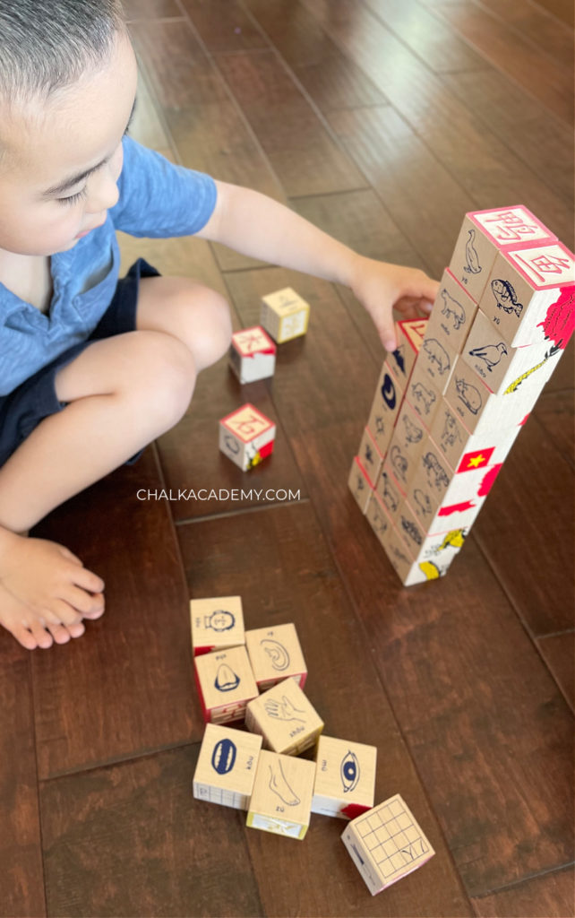 Child playing and learning with bilingual Uncle Goose Chinese character English, Pinyin wood blocks