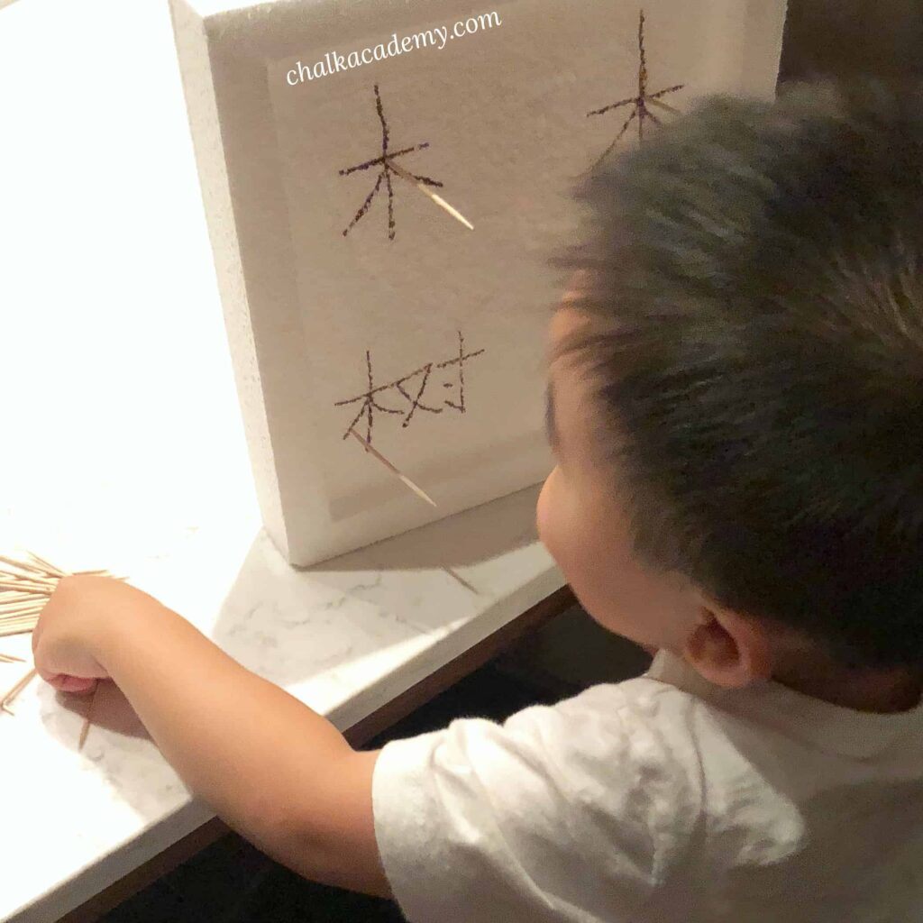 Poking Chinese characters in polystyrene with toothpicks