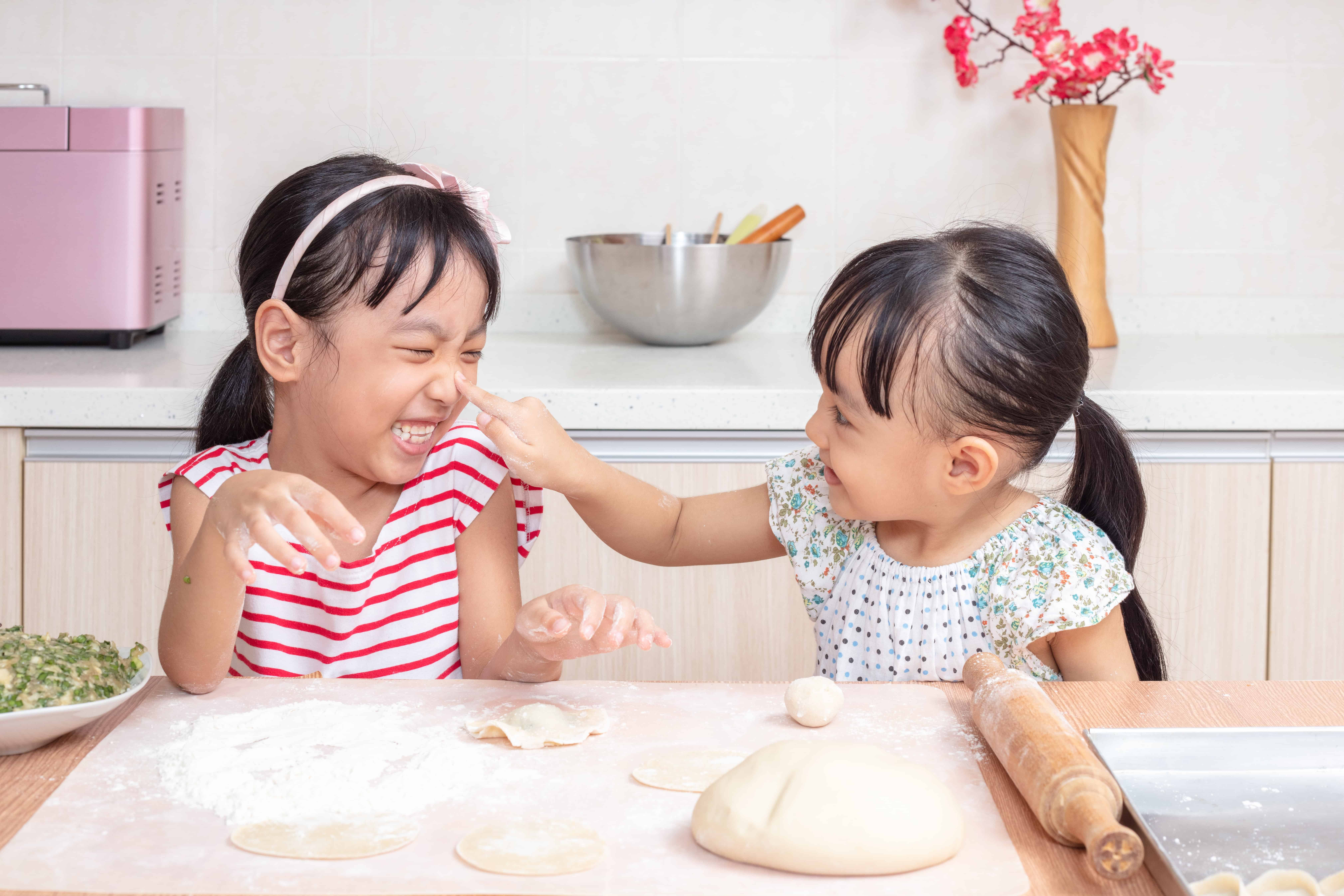 Asian Chinese little sisters making dumpling in the kitchen at home