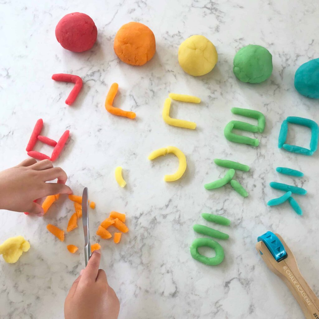 Cutting colorful playdough Hangul letters