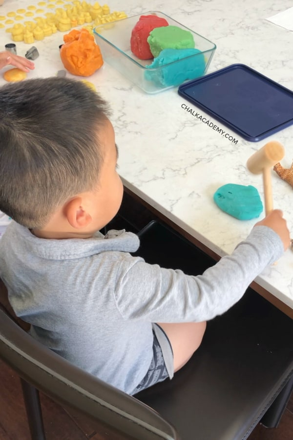 Hammering playdough with a small wooden mallet
