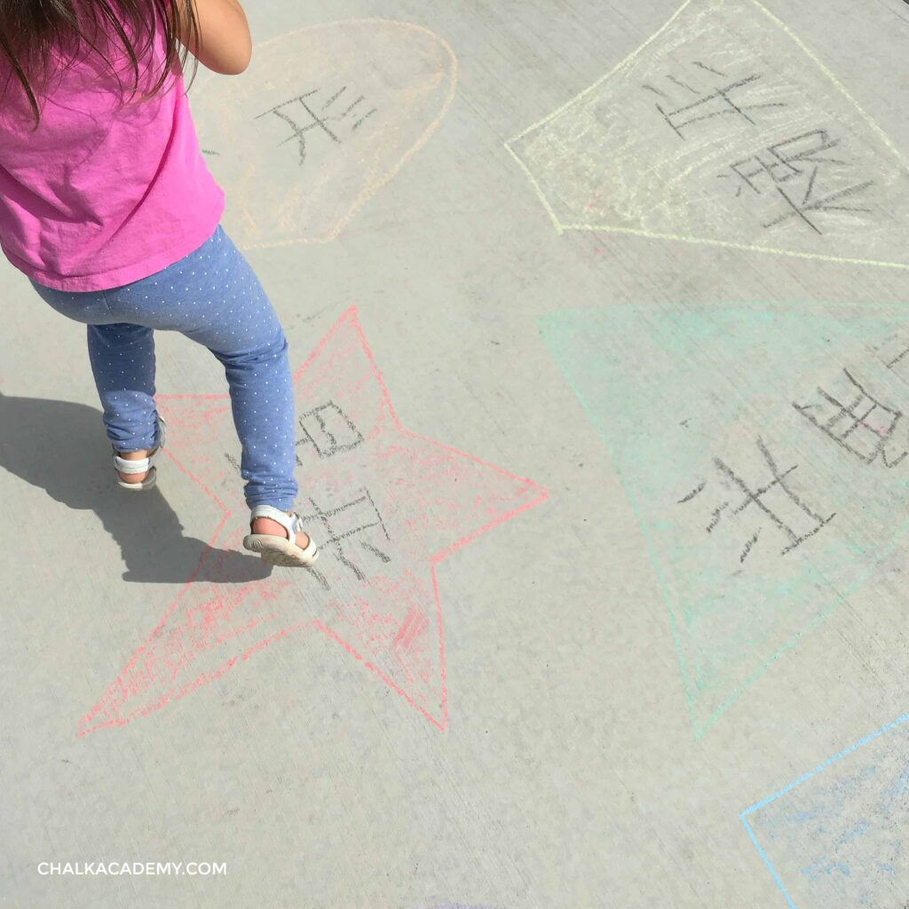 Jumping on sidewalk chalk shapes outside and learning Chinese