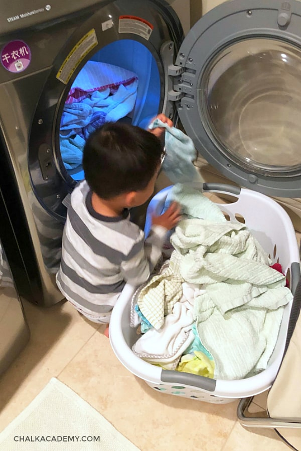 Toddler son helping unload clean laundry from drying machine