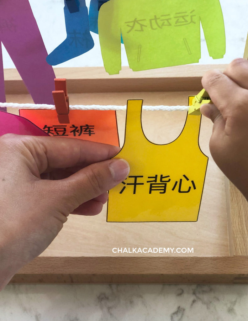 Hanging yellow tank top with Chinese characters onto clothesline with yellow clothespin.  Toddler song needed some help with fine motor skills.