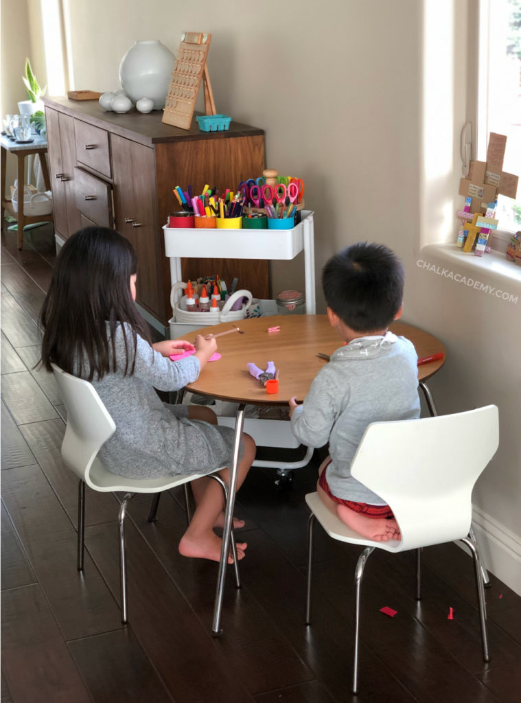 Art space for children; girl and boy sitting quietly at small round table creating art #artspace