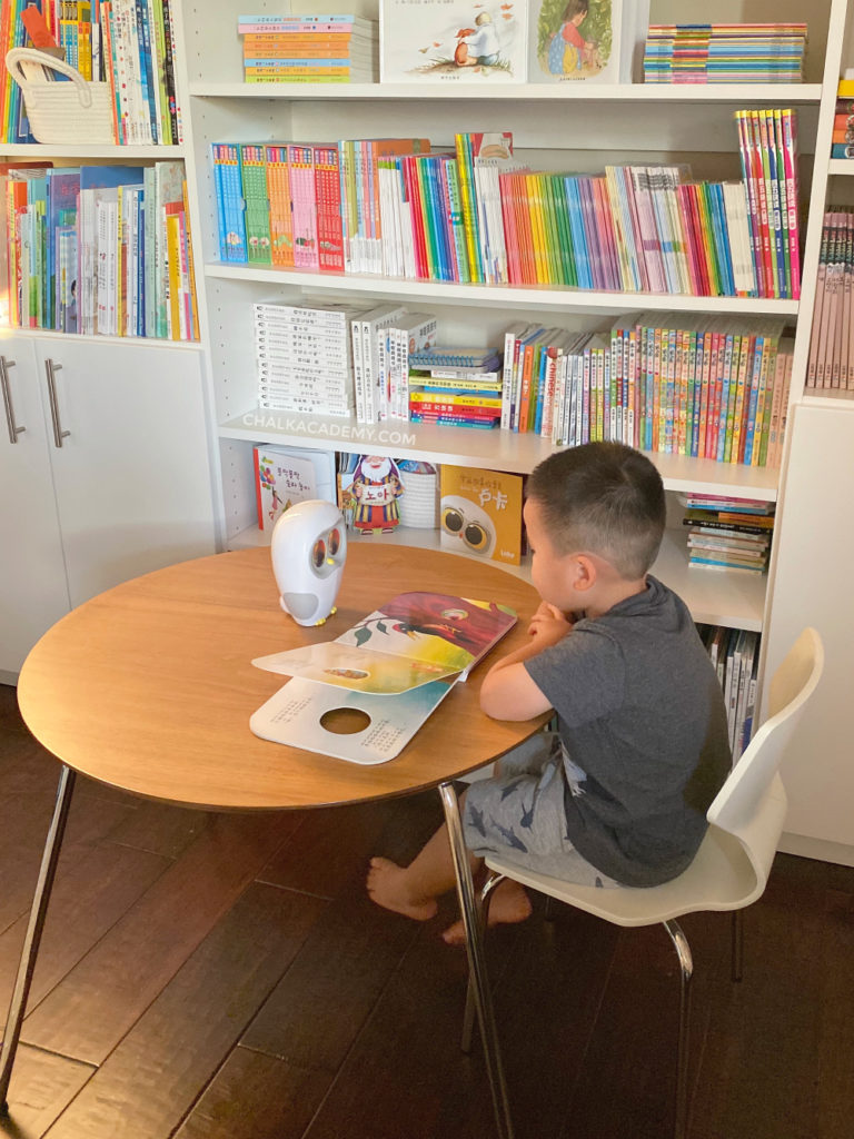 Reading Chinese books in modern home kids library with Luka Reading Robot