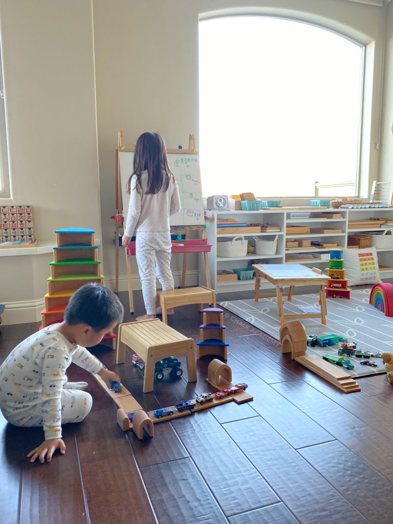 Organized, modern play area and homeschool room: Son playing with blocks and toy cars; bamboo stepstools are use for sitting and also play; tray table for my daughter's homework; white custom shelf inspired by IKEA Besta