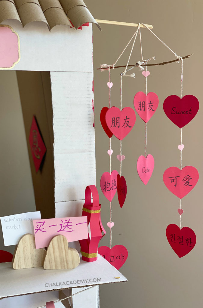 DIY heart mobile for Valentine's Day! Made of 2 twigs, cotton twine string, hearts cut from card stock paper with Chinese, English, and Korean words!