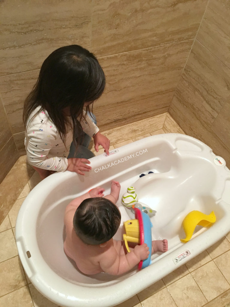 Big sister helping bathe little brother