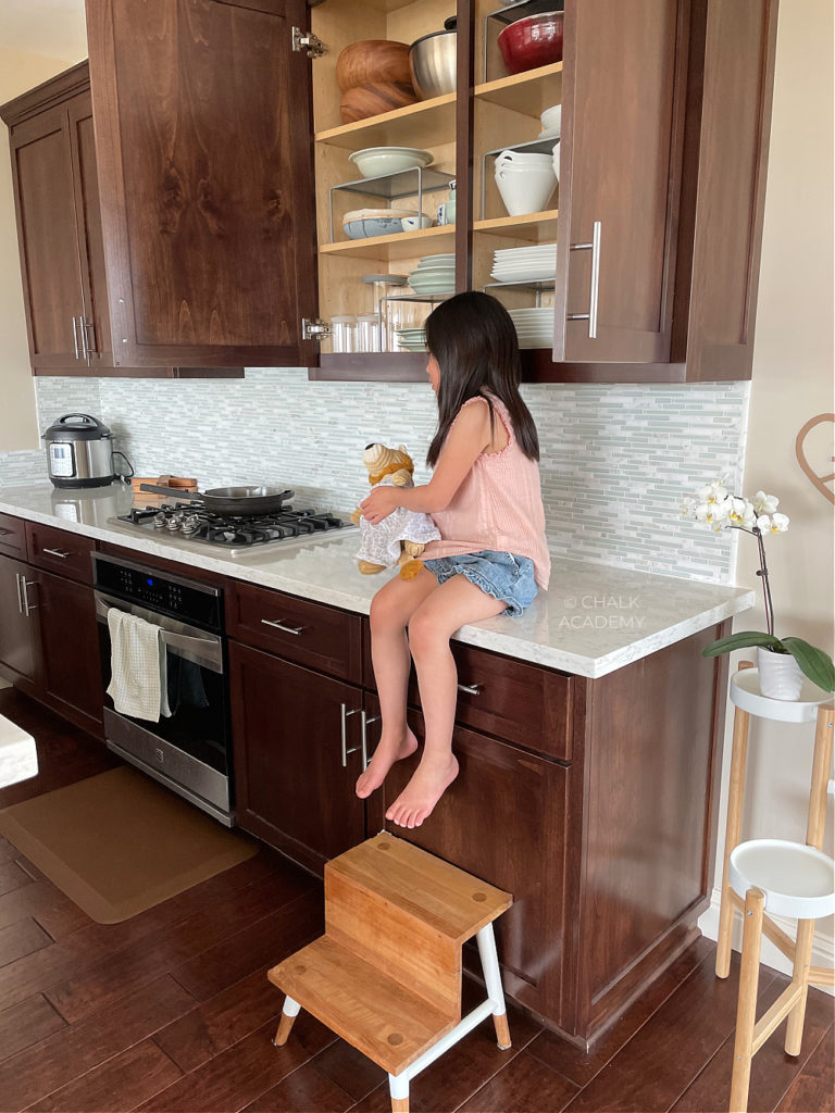 Organized kitchen with dark brown cabinets and white marbled quartz countertops; How We Keep our Kitchen Safe and Organized with Kids