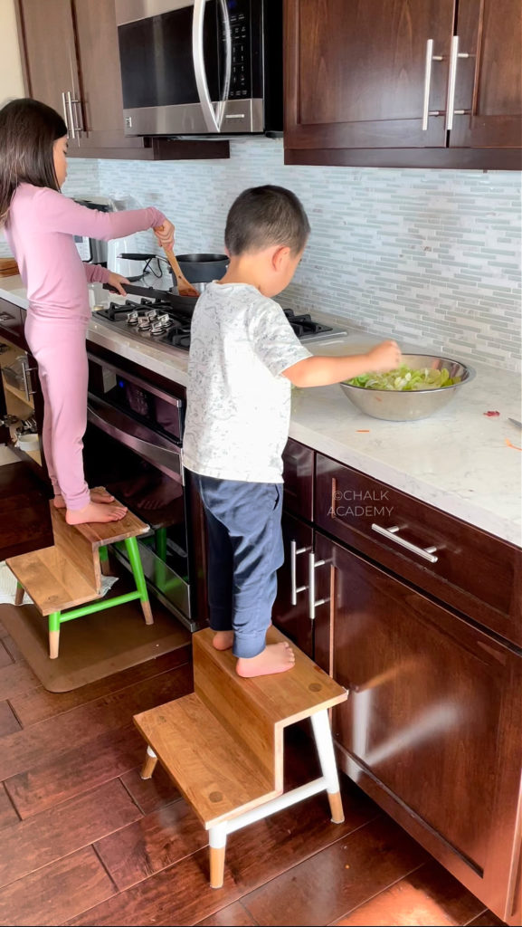 Kids cooking in the kitchen with Serena and Lily teak wood stepstools; dark cabinets, white marbled quartz countertops