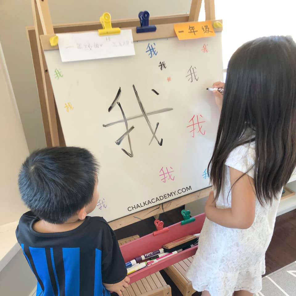 Kids writing Chinese characters on an easel