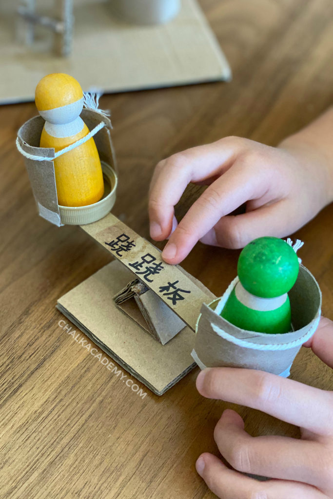 DIY Toy see-saw made with cardboard, toilet paper rolls, and bottle caps