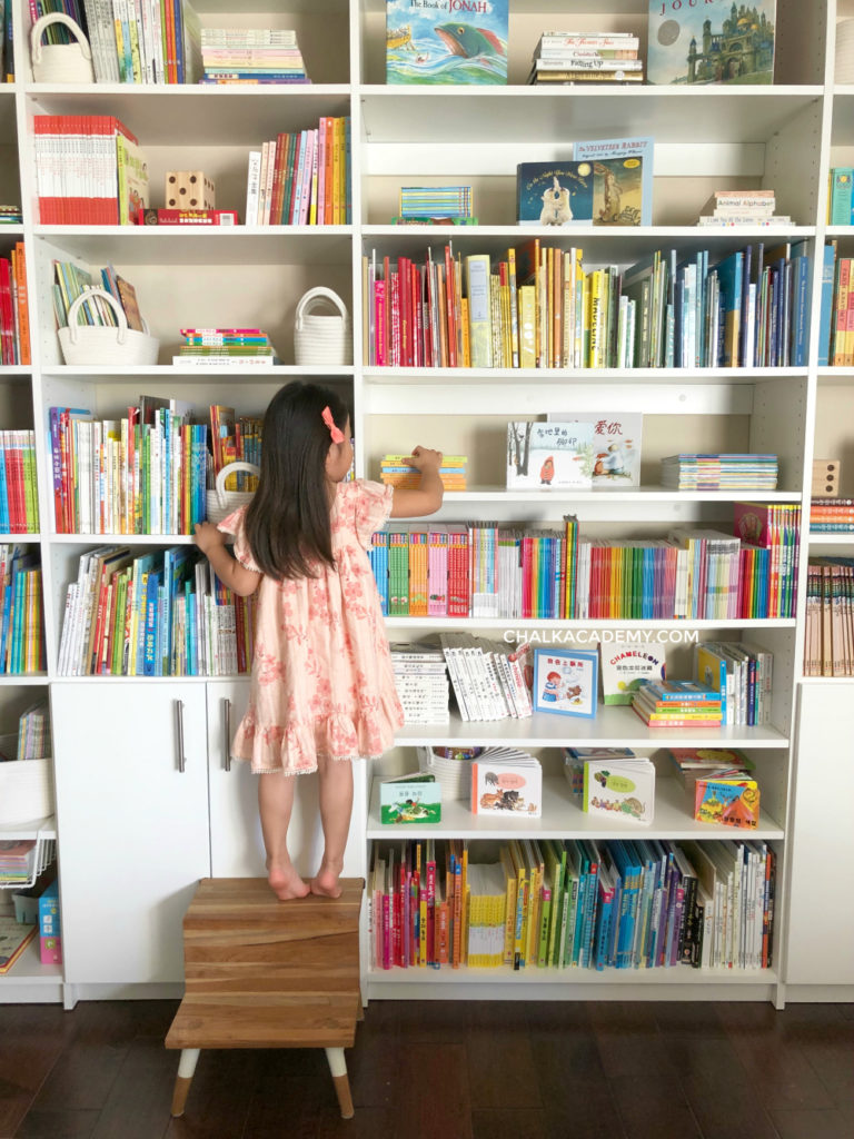 Modern library bedroom with white shelves: Former closet replaced by adjustable bookshelves; Serena & Lily step stool