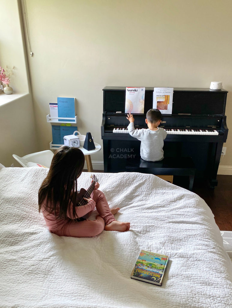 Daughter trying to play ukulele, son banging on the piano!