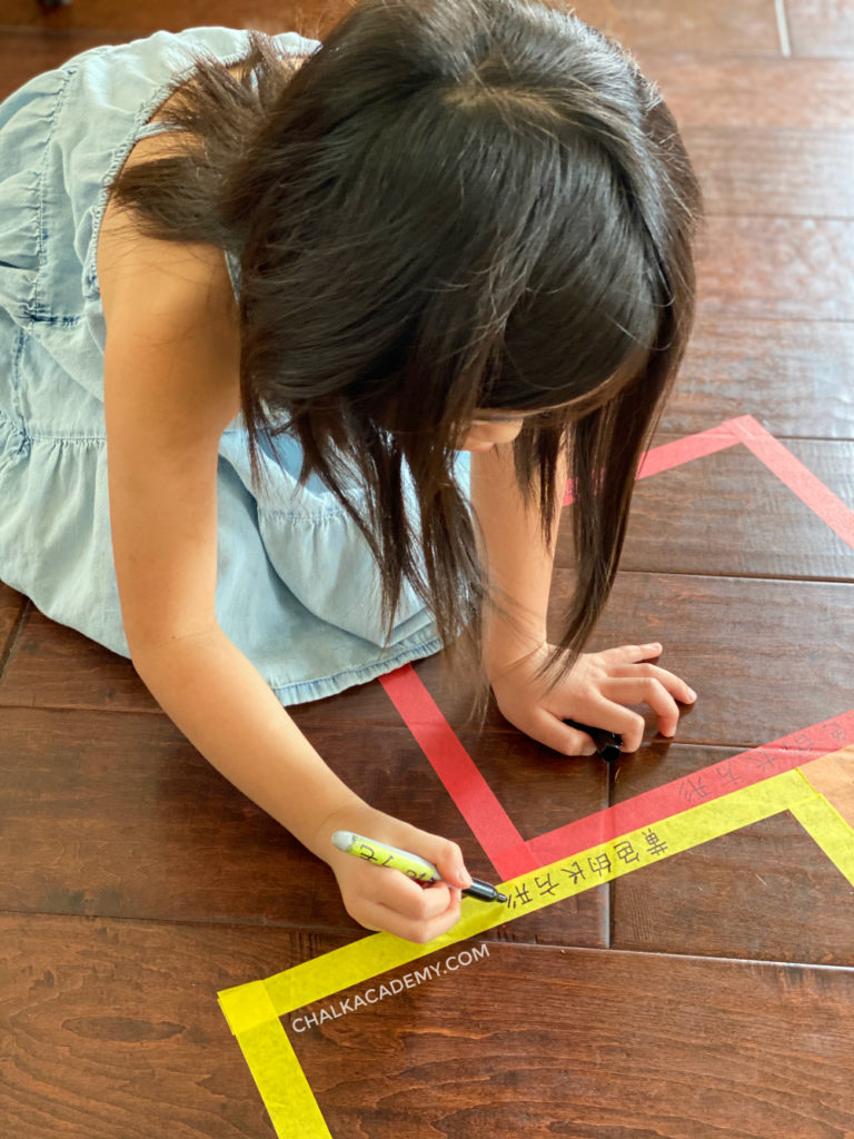 6 year old girl writing Chinese characters on painter's tape