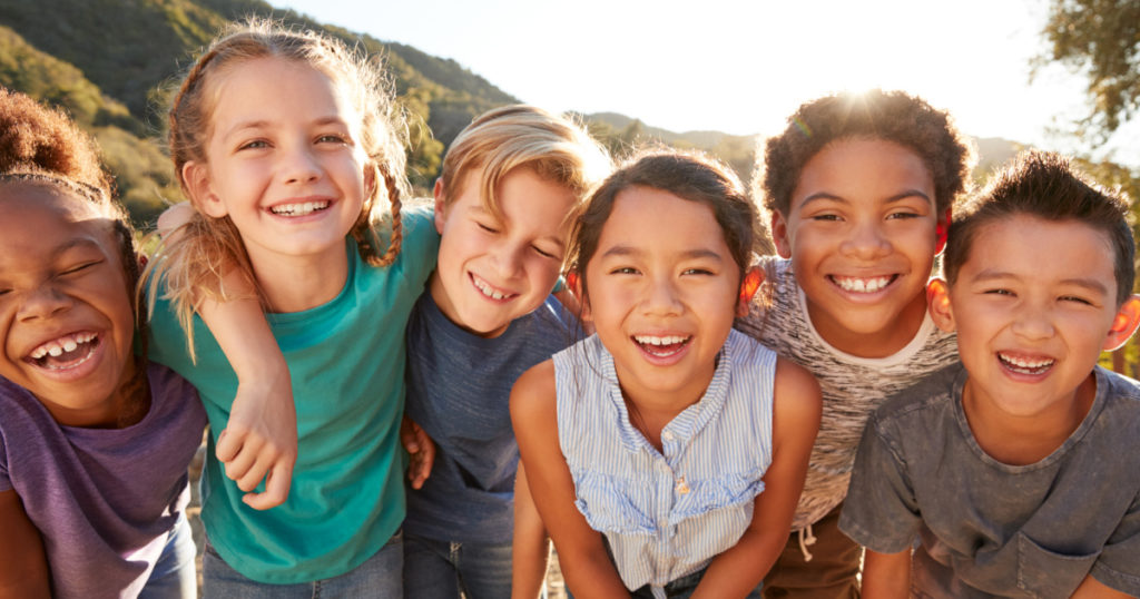 Diverse kids of various races playing and smiling happy together; How to Talk to Kids About Racism Today | Inclusive, Bilingual Resources