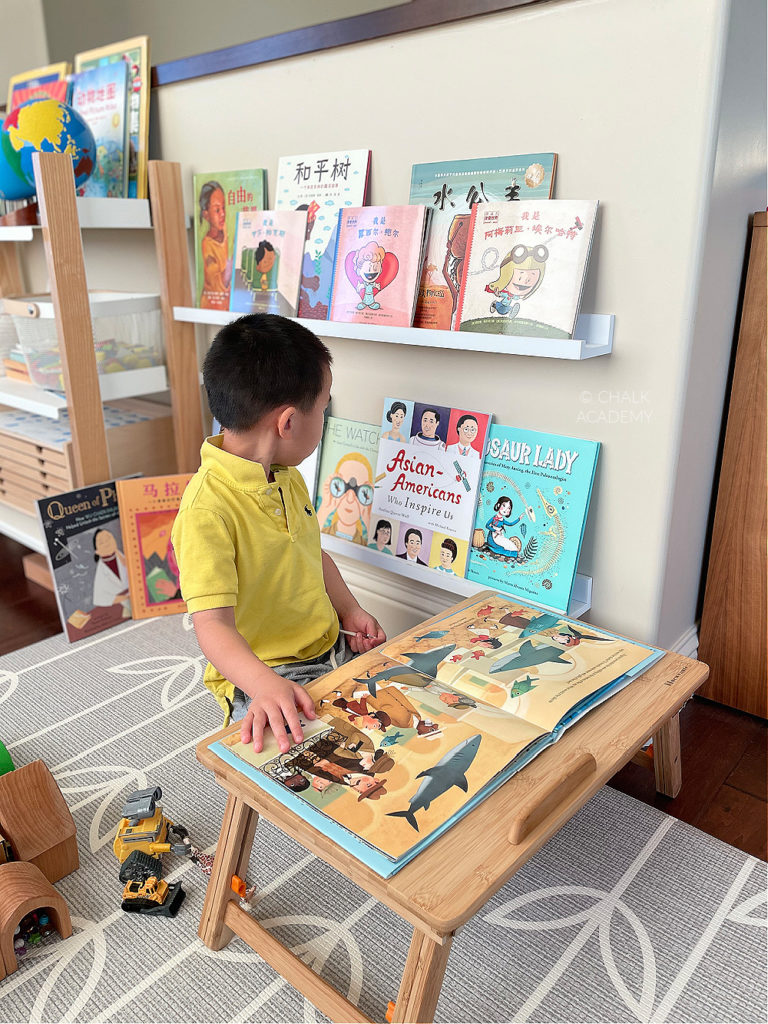 Son filpping through Women's History books in Chinese and English; floating wall book ledge; reading corner